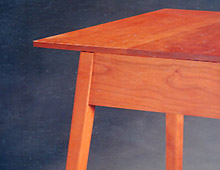 This is a night stand or lamp table in cherry wood. The top is square and the legs are slightly flared out, as an easel.