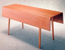 This is a great long harvest table in cherry wood. The table has two drop-leaves and slightly flared legs.