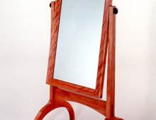 This is a stand-up mirror in cherry wood. It has a swiveling rectangular mirror and large curving legs.