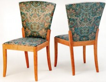 This is part of a dining set: two armless chairs upholstered in a green paisley-based brocade.
