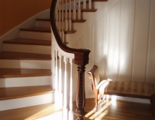 These are some square-top stair spindles, painted fresh white to contrast with the dark and ornately carved newel post.