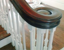 This is a hand rail volute in mahogany. The rail sits atop painted square-top spindles. The classic scroll design adds a grounding element to this airy, sun-filled foyer.