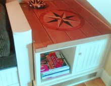 This is a custom, built-in coffee table with a compass rose inlay on top and a shelf and cabinet below. This table is being enjoyed at the New Castle home from Photo 12.